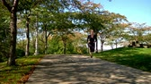 runners : A young woman jogs at the West End Overlook in Pittsburgh on a sunny Autumn day.