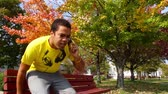 concentrando : A young man talks on his cell phone in the park. Stock Footage
