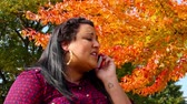 concentrando : A young woman talks on her cell phone in the park. Stock Footage