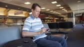 verificar : A man uses his smartphone in the airport.