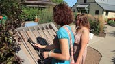 improvise : Two young woman play a musical instrument outside at Hershey Gardens.