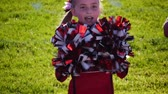 saúde : A young girl cheerleader on the sidelines cheers with her pompoms. Stock Footage