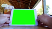 tablet počítač : A man uses a tablet computer at a restaurant.  Green screen and corner markers included for advanced motion tracking.
