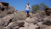 runners : A young man jogs down a desert landscape.  Slow motion.