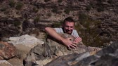 stráň : A young man pretends to climb up a cliff in the desert. Dostupné videozáznamy