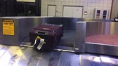 поездка : Baggage falls onto the conveyer belt in an airport baggage claim area.