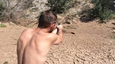 stráň : A young man shoots a pistol in the desert.  Shot at 120fps for super slow motion action.