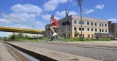 előkészített : A man looks both ways before crossing a railroad crossing on his bike. Stock mozgókép