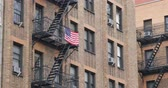 big apple :  An American flag hangs from the fire escape on a typical New York style apartment building establishing shot. Stock Footage