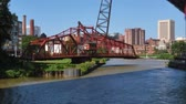 engenharia :  A draw bridge closes after a tour boat passes on the Cuyahoga River in Cleveland, Ohio.
