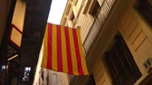 erkély :  A Catalonia flag hangs between two buildings in the Gothic District of Barcelona. Stock mozgókép