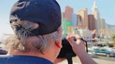 kasino : A male tourist takes a photograph of the New York New York casino in Las Vegas.