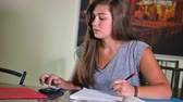 перегружены : 6429 A frustrated teenager does her homework in the kitchen. Стоковые видеозаписи