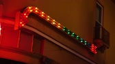 bars :  A colorful arrow points on the side of a building at night.