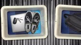 tecnologia : Various personal items from passengers pass by in bins on their way into the x-ray machine at an airport security checkpoint station.