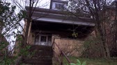 creepy : An establishing low angle shot of an old, abandoned home.