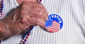 naklejka : An elderly woman puts an I Voted sticker on her shirt.