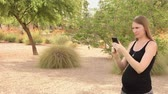 app : A young woman plays an augmented reality game on a smartphone outside in a typical Arizona public park.