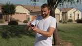 app : A young man plays an augmented reality game on a smartphone in a typical Arizona neighborhood.