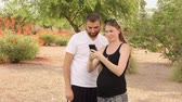app : Two millennials play an augment reality game on a smartphone in a typical Arizona public park. Stock Footage