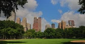 A daytime summer establishing shot of apartment buildings on Central Park West near Central Park.