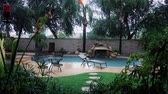 A daytime establishing shot of an Arizona residence backyard pool in a monsoon or rain storm. Stock Footage