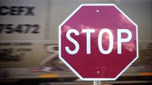 A red stop sign at a railroad crossing while a cargo train passes behind. With audio.