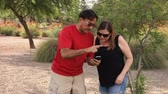 app : Two adults play the popular augmented reality game  outside in a public park.