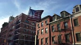 A tattered American flag flaps in the wind in front of apartment buildings in New Yorks Little Italy neighborhood.