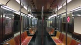 An interior establishing shot of an empty New York City subway car as it travels along the tracks. Loopable, with signage digitally removed.