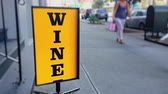 An eye-catching spinning WINE advertisement sign on the sidewalk outside of a liquor store in a large city.