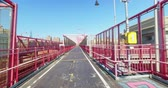 A personal perspective view walking or riding on the pedestrian sidewalk portion of the Williamsburg Bridge over the East River between Manhattan and Brooklyn. Stock Footage