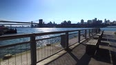 A daytime morning establishing shot of Brooklyn skyline and Bridge as seen from Pier 15 East River Esplanade.