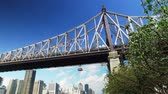 A low angle daytime establishing shot of the Ed Koch Queensboro Bridge with the Roosevelt Island Tram traveling beside.