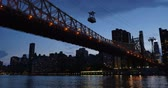 An evening establishing shot of the Ed Koch Queensboro Bridge between Manhattan and Brooklyn as the Roosevelt Island Tram carries passengers over the East River. Stock Footage