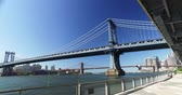 A daytime establishing shot of the Manhattan Bridge over the East River between Manhattan and Brooklyn.