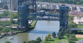 ferrugem : A time lapse view of a tour boat carrying tourists under a drawbridge on the Cuyahoga River in Cleveland.