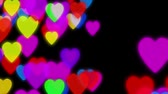 mind : Hearts background animation. Colorful hearts slowly falling down on a dark background with particles flowing around Stock Footage