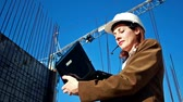 arquitetônico : Builder engineer ;female builder engineer is considering a plan for new construction on a laptop,video clip Stock Footage