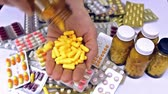 проливая : pouring pills in hand ; pouring a lot of pills from the medicine bottle in female hand,video clip
