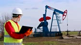 petrokimya : Oil worker check pump jack ; Oil worker controls the operation of the oil pump using a laptop,video clip Stok Video