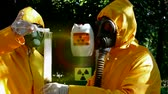 dispositivo : Tempestuous chemical reaction;Two chemical technicians with gas masks and protective suits carried out disposal of toxic substances,video clip