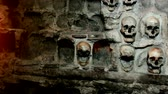 color : Wall of human skulls ; Human skull built into the stone wall,  video clip with light effects