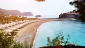 den : Sandy beach bathed in the morning sun ; St. Stephen, Montenegro, 25th August 2017: View of the beautiful island Saint Stephen in Montenegro, 4 K Video Dostupné videozáznamy