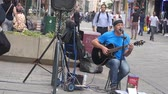 Old Man In Blue Shirt Busking In City Streets - Movement - Left To Right