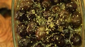 thyme : Falling fresh thyme leaves on to black olives on rotate