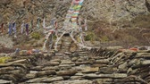 muren : Coloured prayer flags flapping above stone stairs to Milarepa cave, Nepal Stockvideo