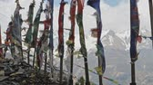 山頂 : Coloured prayer flags on poles flap against severe snow mountains, Nepal 動画素材