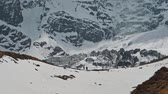muren : Tourists stand near huge glacier at foot of snow Annapurna III mountain , Nepal