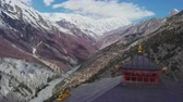 山頂 : Clouds shadows crawl over snowy mountain slope, Tilicho Peak, red pagoda, Nepal 動画素材